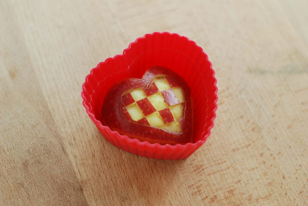 this is a picture of a red apple cut into a heart shape. Read more a t beneficial-bento.com